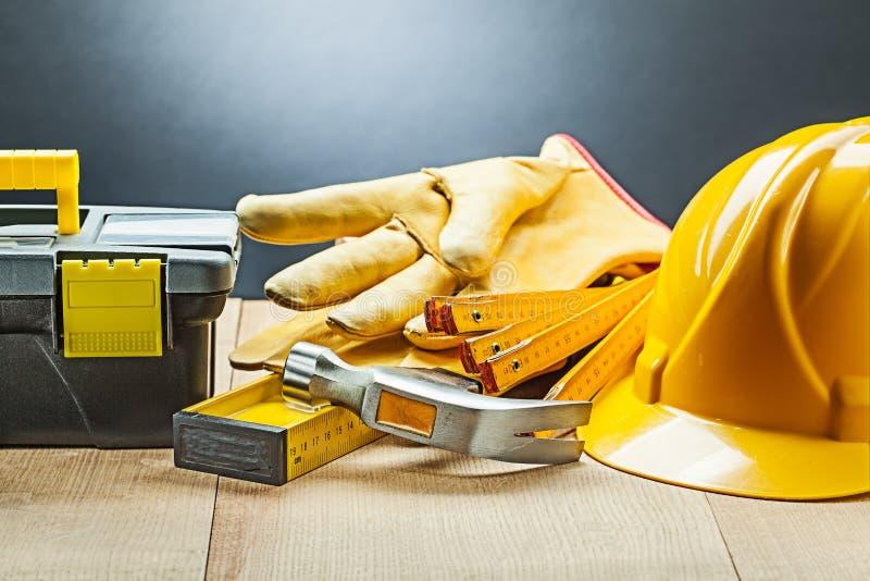 Black tool box gloves hammer level wooden meter helmet stock photography