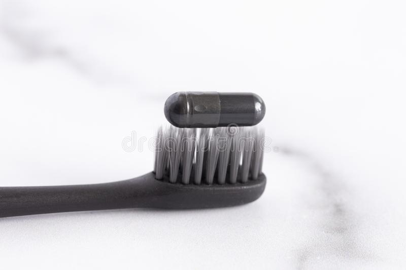 Black Toothbrush with an Activated Charcoal Pill on Top. A Black Toothbrush with an Activated Charcoal Pill on Top royalty free stock photo