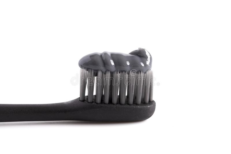 A Black Toothbrush with Black Activated Charcoal Toothpaste on a White Background. Black Toothbrush with Black Activated Charcoal Toothpaste on a White stock image