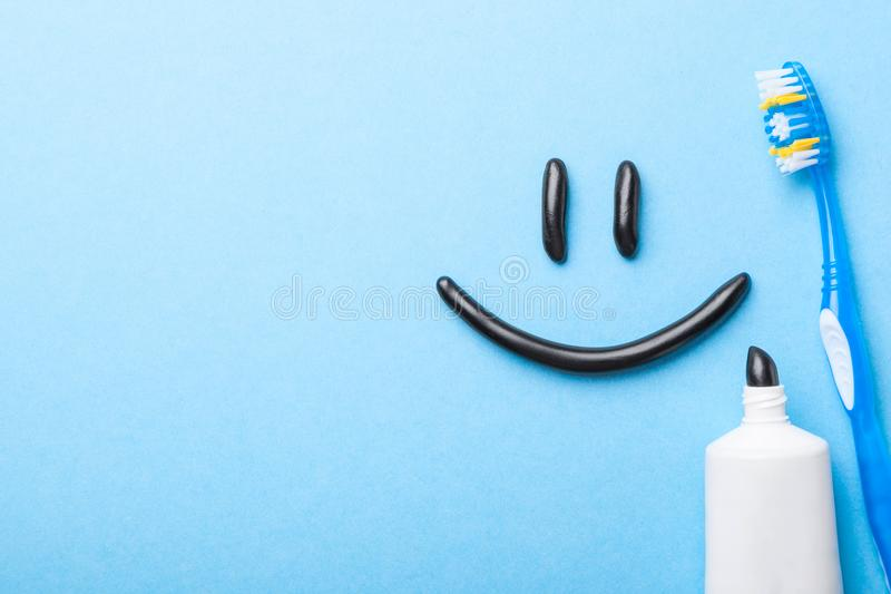 Black toothpaste from charcoal for white teeth. Toothpaste in the form of smile on the face, tube and toothbrush on blue stock photography