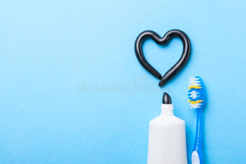 Black toothpaste from charcoal for white teeth. Tooth-paste in the form of heart, tube and toothbrush on blue background. Copy space for text stock image