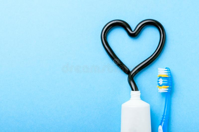 Black toothpaste from charcoal for white teeth. Tooth-paste in the form of heart, tube and toothbrush on blue background. Copy space for text royalty free stock images
