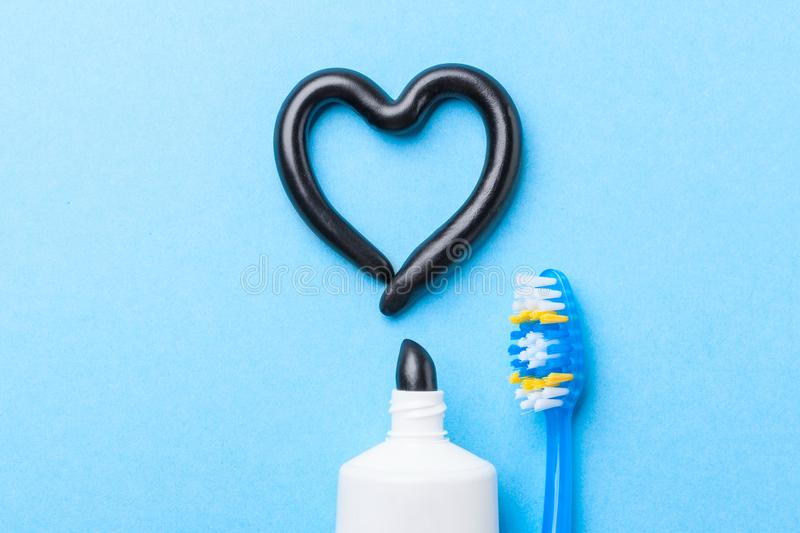 Black toothpaste from charcoal for white teeth. Tooth-paste in the form of heart, tube and toothbrush on blue. Background royalty free stock image