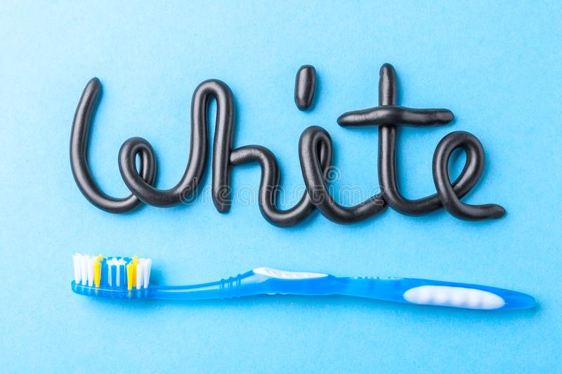Black toothpaste from charcoal for white teeth. Word WHITE from black toothpaste and toothbrush on blue. stock photography