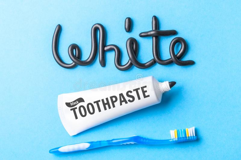 Black toothpaste from charcoal for white teeth. Word WHITE from black toothpaste, tube and toothbrush on blue stock photography