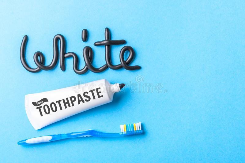 Black toothpaste from charcoal for white teeth. Word WHITE from black toothpaste, tube and toothbrush on blue. Background. Copy space for text stock images