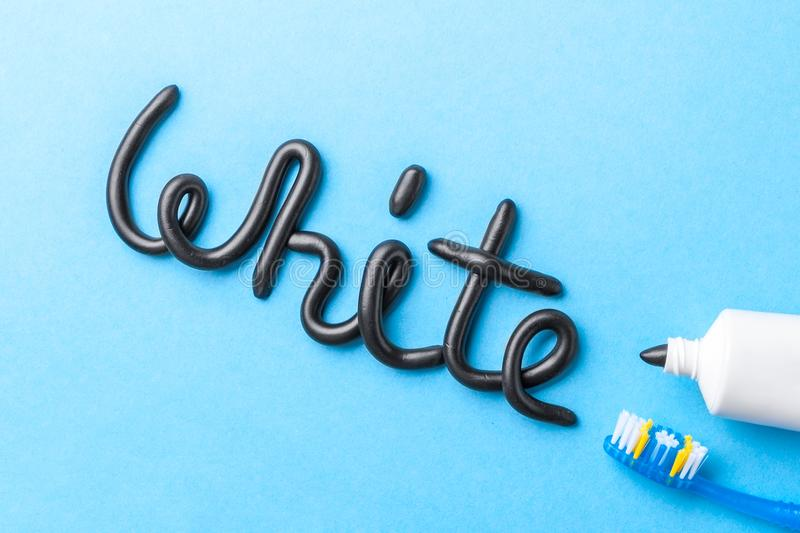 Black toothpaste from charcoal for white teeth. Word WHITE from black toothpaste, tube and toothbrush on blue royalty free stock photo