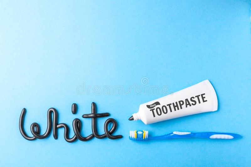 Black toothpaste from charcoal for white teeth. Word WHITE from black toothpaste, tube and toothbrush on blue stock image