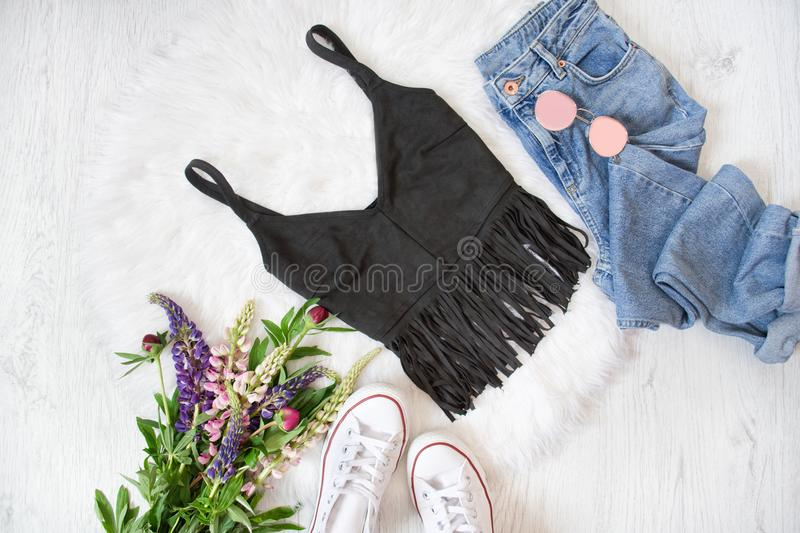 Black top with fringe, blue jeans, white sneakers. Bouquet of wi. Ld flowers. White background. Fashionable concept royalty free stock image