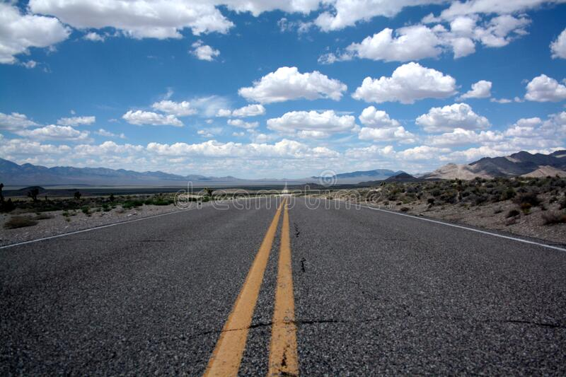 Black Top Road Under Clear Blue Cloudy Sky stock photo