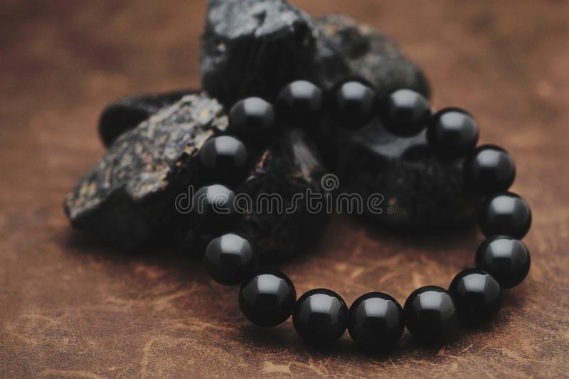 Black tourmaline bracelet. And several tourmaline minerals on leather background royalty free stock photo