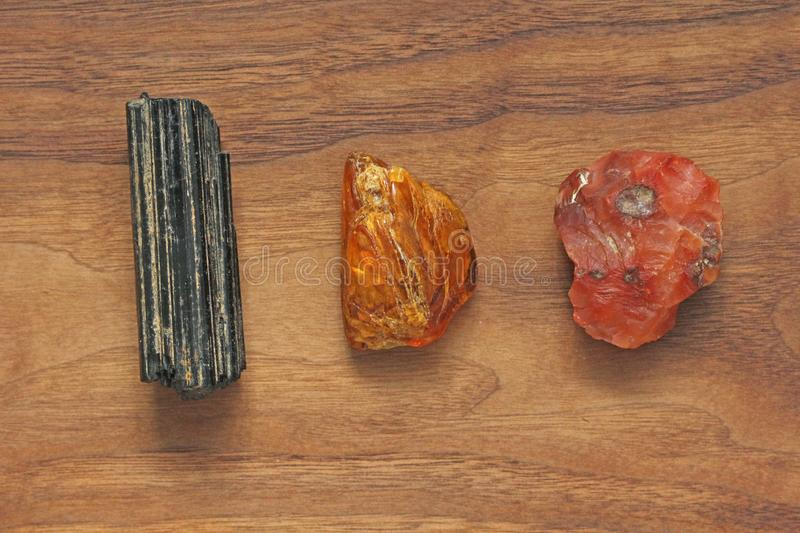 Black tourmaline, Sherl, Carnelian, Amber. Collection of natural. Stones of minerals on a background of natural wood American black walnut. Beautiful untreated stock image