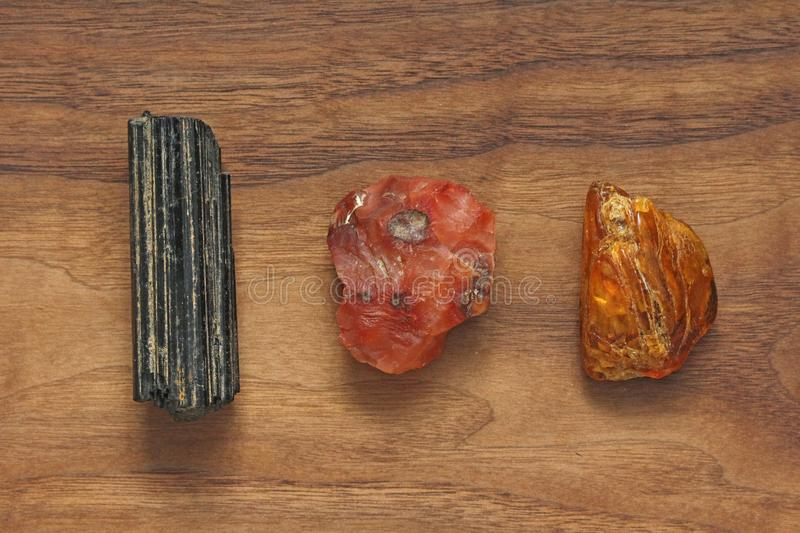 Black tourmaline, Sherl, Carnelian, Amber. Collection of natural. Stones of minerals on a background of natural wood American black walnut. Beautiful untreated stock photo