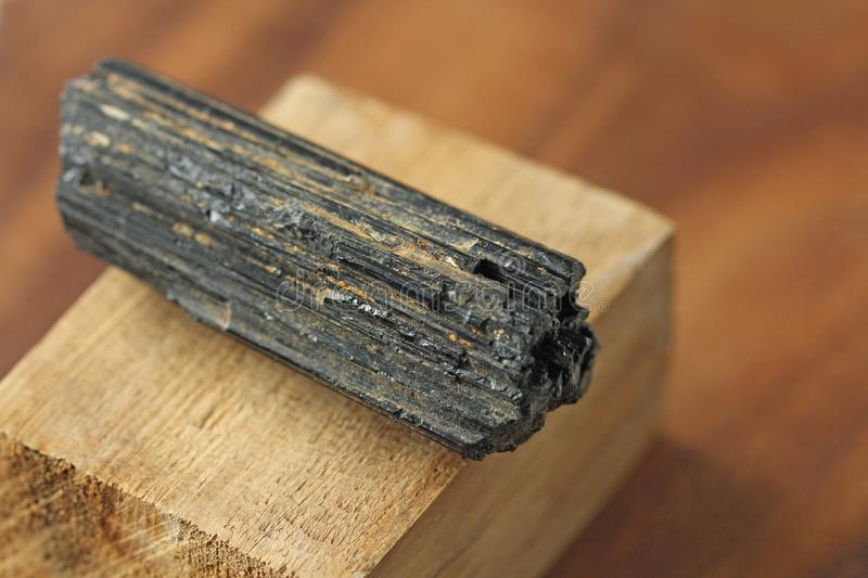 Black tourmaline stone on a background of natural wood American. Black walnut. Mineral collection stones. Stone is a sherl tourmaline. Black Crystal stock photography