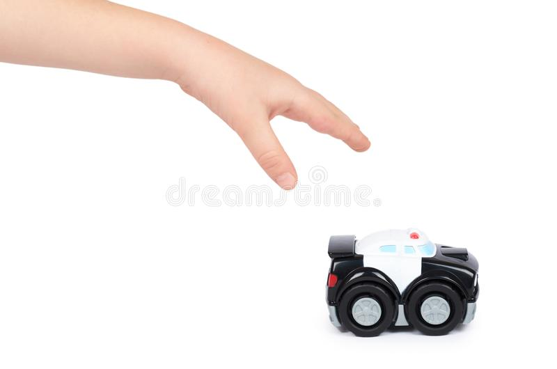Black toy police car with kid hand, isolated on white background.  stock photos