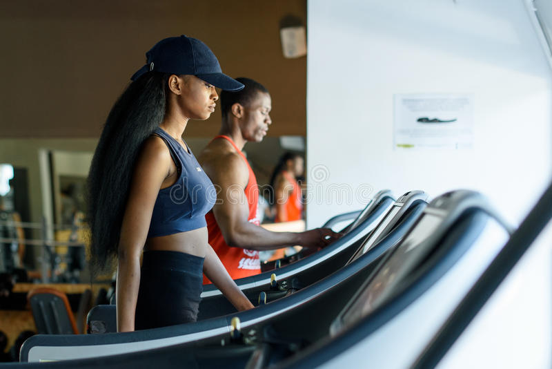 Black trainer and african american woman on the treadmill in gym. Fitness concept royalty free stock images