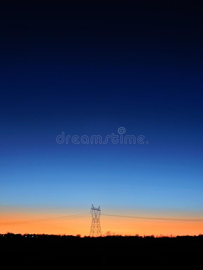 Black Transmitter Tower Under Blue and Orange Sky stock images