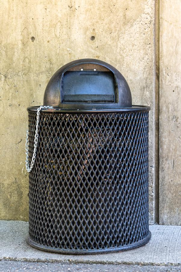 Black trash can in public park against a concrete wall, metal grate for base and plastic bubble lid held to base by a chain stock photography