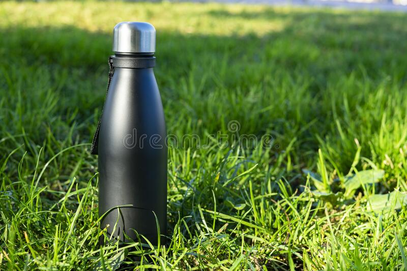 Black travel thermos on a green grassy background. Thermo concept royalty free stock image