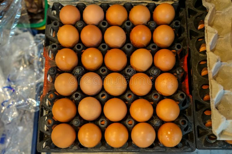 Black trays full of natural light brown chicken eggs selling in local food market, top view selective focus stock image