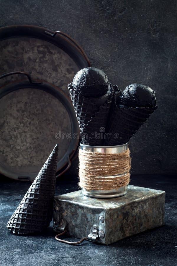 Black trendy ice cream in black waffle icecream cones. royalty free stock photography