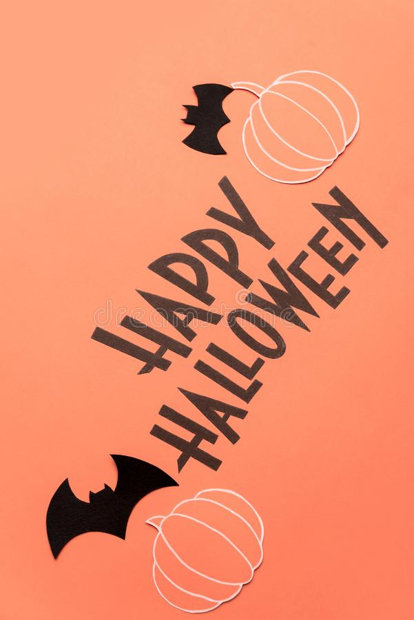 Hand written phrase Happy Halloween with pumpkins and bats near it royalty free stock photo