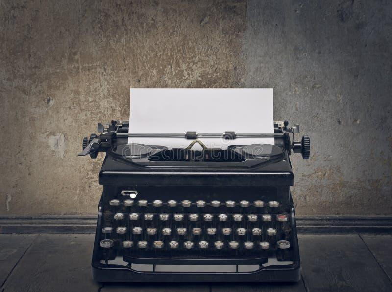 Typewriter. Black typewriter with white paper in the street royalty free stock photos