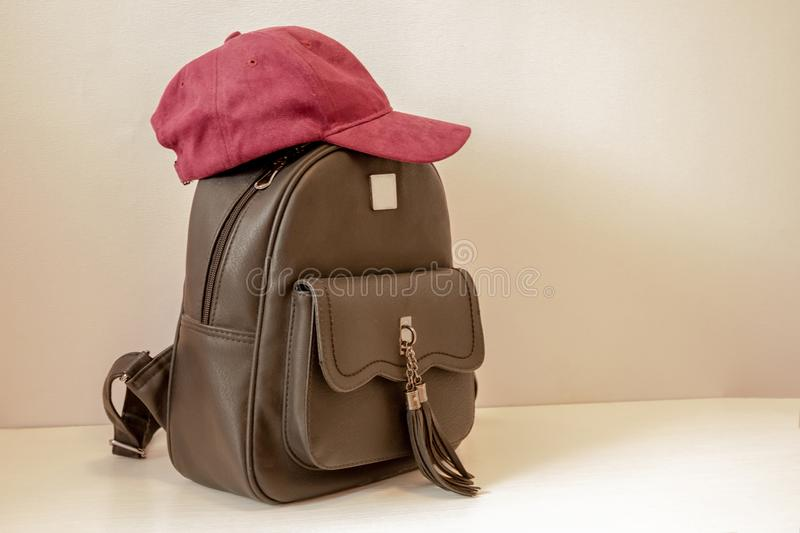Backpack and cap for the girl. Black, urban backpack for a young girl on a light background. Top with raspberry cap. Modern style. Teenage fashion stock photo