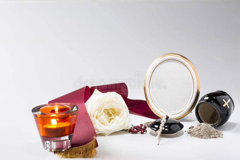 Black urn with red tape,white rose, candle, rosary for sympathy. Card on bright background royalty free stock images