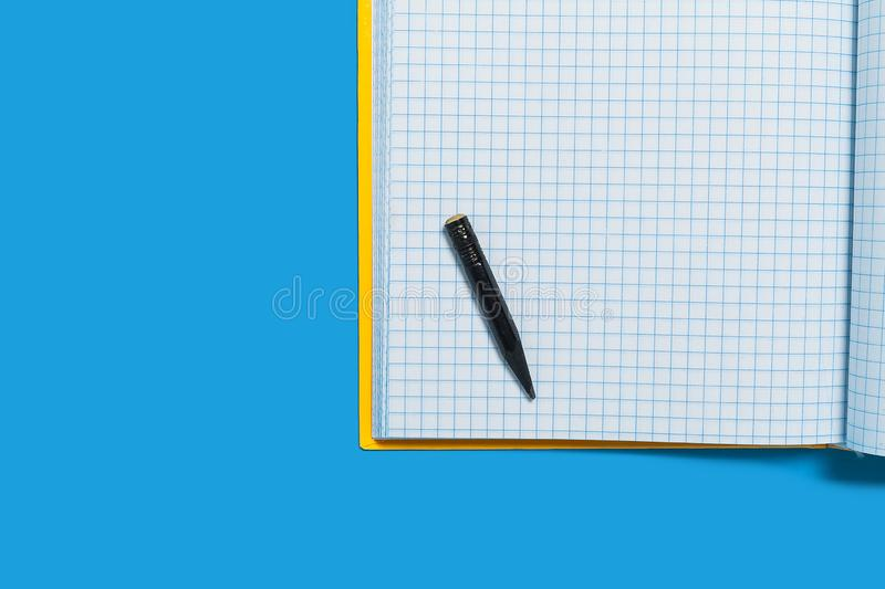 Black used pencil lying on a workbook. Black tiny used pencil lying on the white copybook. concept of office and educational chancery. free copyspace stock images