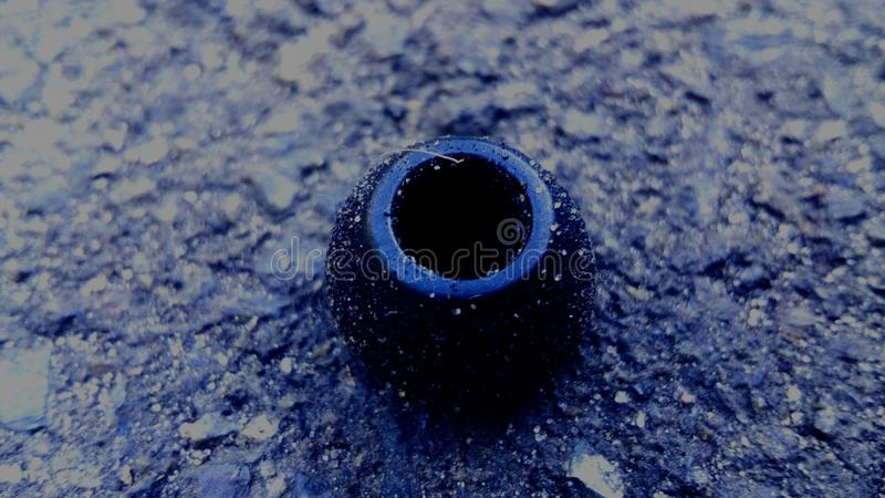 Vacuum from earphone. Black vacuum from the earphone in the sand on the asphalt stock image