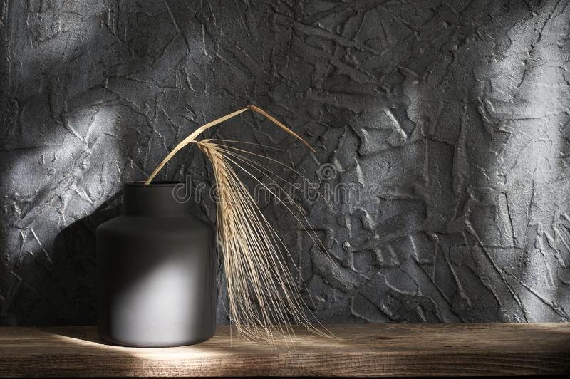 Black vase with ear, home decor. Black vase with ear on distressed wooden shelf against rough plaster dark grey wall in sunlight. Home decor royalty free stock image