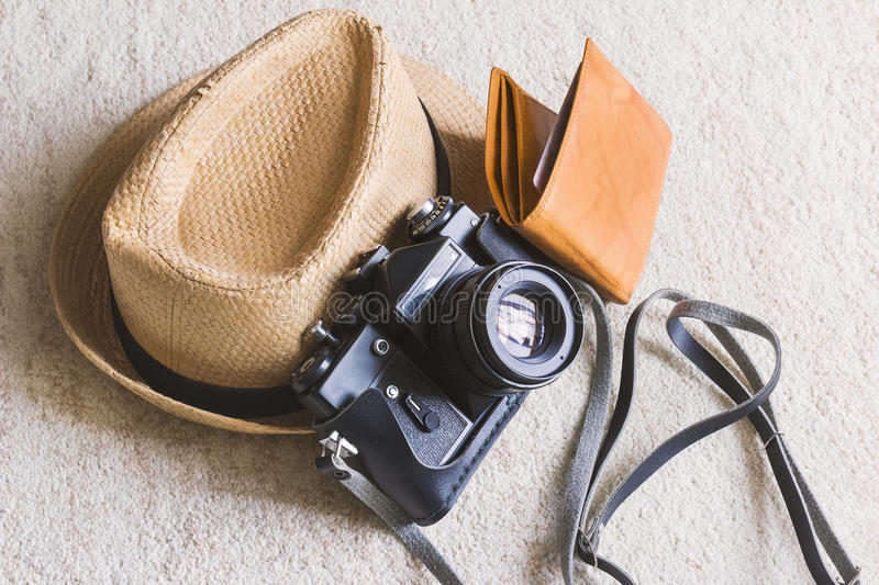 Travel concept, straw hat/boater with black vintage camera and brown wallet. Black vintage camera, hat, wallet, daylight stock photography