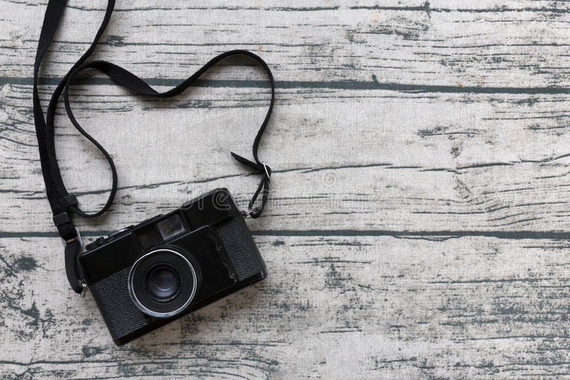 Black vintage camera on old wood print tablecloth background. To. P view and copy space stock images