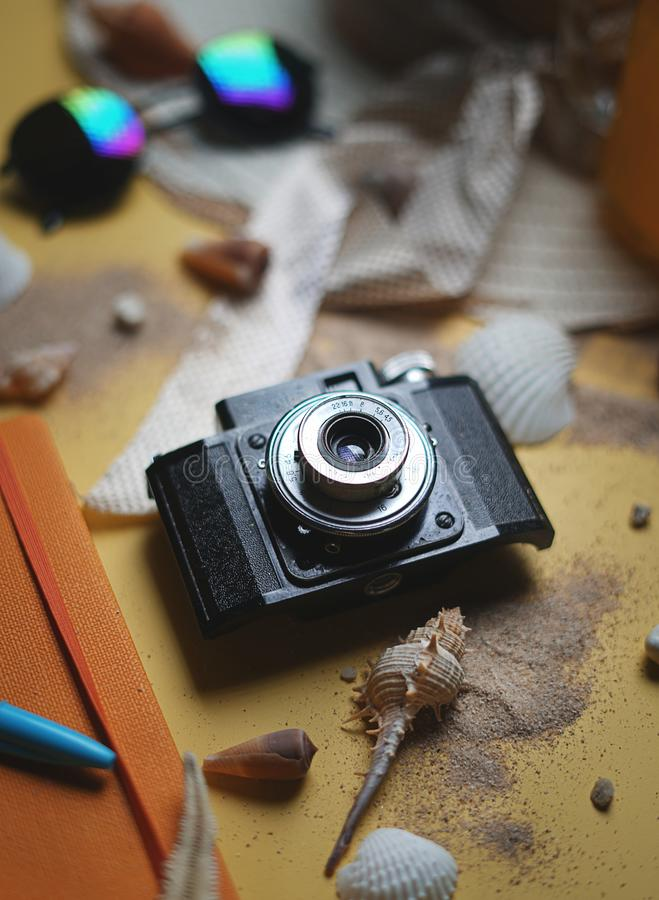 Black Vintage Camera Between Summer Beach Accessories on Yellow. Background stock image