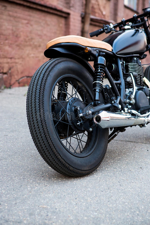 Black vintage custom motorcycle cafe racer. Black vintage custom motorcycle motorbike caferacer in front of brick wall. Back view exhaust royalty free stock image