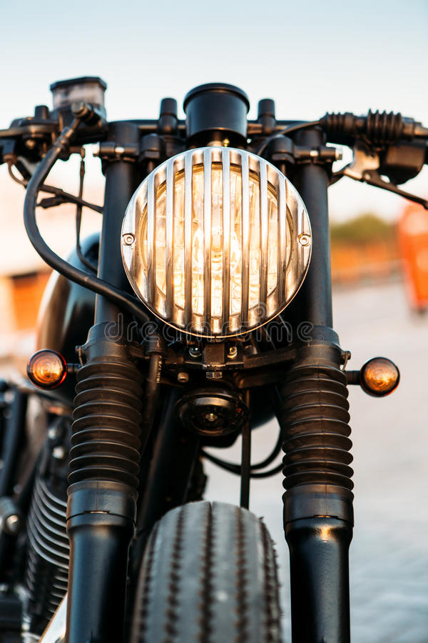 Black vintage custom motorcycle cafe racer. One vintage custom motorcycle cafe racer motorbike with grill headlight on empty rooftop parking lot during sunset royalty free stock photography