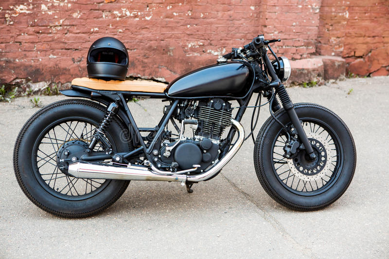 Black vintage custom motorcycle caferacer. Black vintage custom motorcycle motorbike cafe racer with black full face helmet in front of brick wall. Ready for a royalty free stock photos