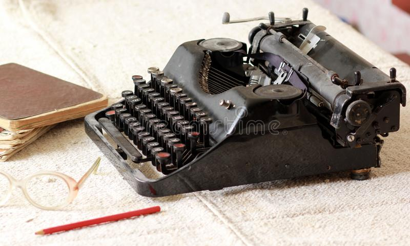 Black vintage metal type writer next to a pile of old note books, pair of eyeglasses and a pencil on a linen tablecloth stock photos
