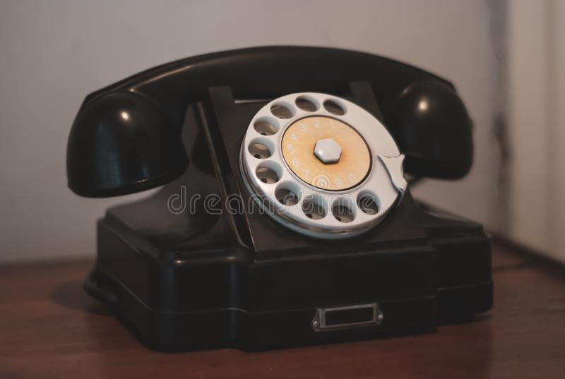 Black vintage rotary dial telephone. Old landline rotary dial telephone; picture is stylized as a vintage photo stock image
