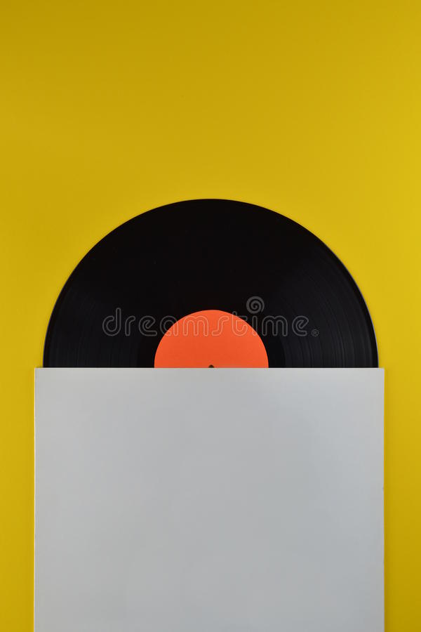 Black vinyl record halfway out of white cover stock photography