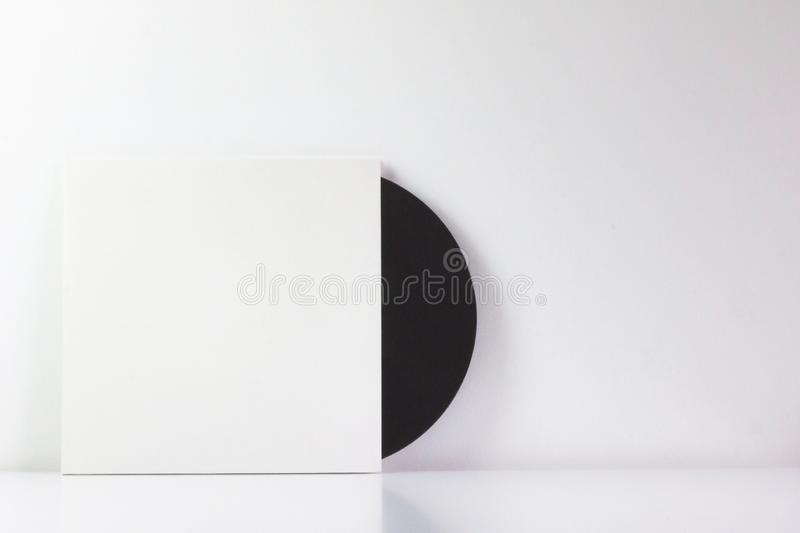 Black vinyl record, in its white box, with blank space to write. With white background. Minimalist photo stock photography