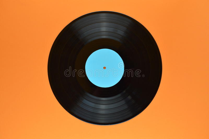 Black vinyl record on orange background. Old black vinyl record with blank cyan label centered on orange background royalty free stock images
