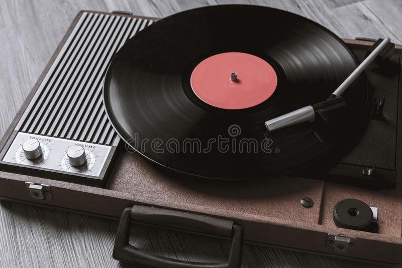 Black vinyl record on record player. Turntable vinyl record player on the background of their gray wooden boards. Needle on a vinyl record. Black vinyl record stock photography