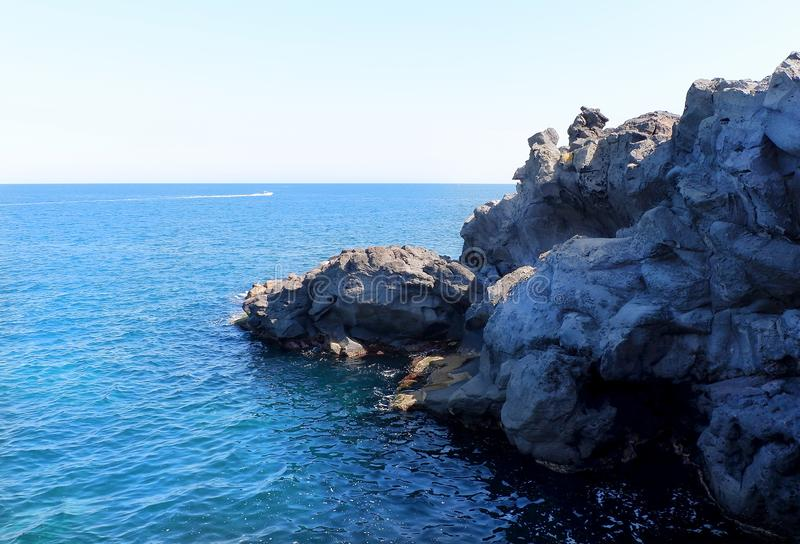 Black volcanic cliffs on the shores of the Mediterranean Sea in Italy. Catania, Sicily royalty free stock photo