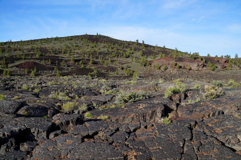 Black volcanic landscape: Cinder cone surrounded by pahoehoe and `a`a lava flows. Three types of black volcanic basalt rock from an eruption of a volcano: cinder stock image