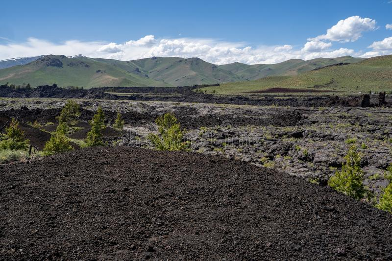 Black volcanic rock and lava flow fields in Craters of the Moon National Monument royalty free stock photography