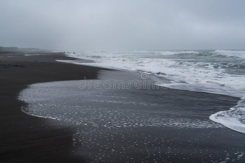 Black volcanic sand at Khalaktyrsky beach of the Pacific at Kamchatka peninsula, near Petropavlovsk-Kamchatsky, Russia stock image