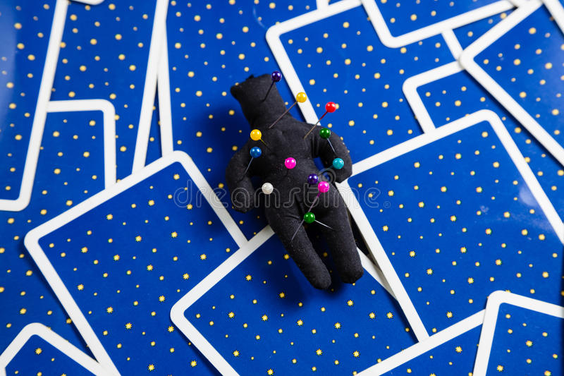 Black voodoo doll on a background of tarot cards. stock images