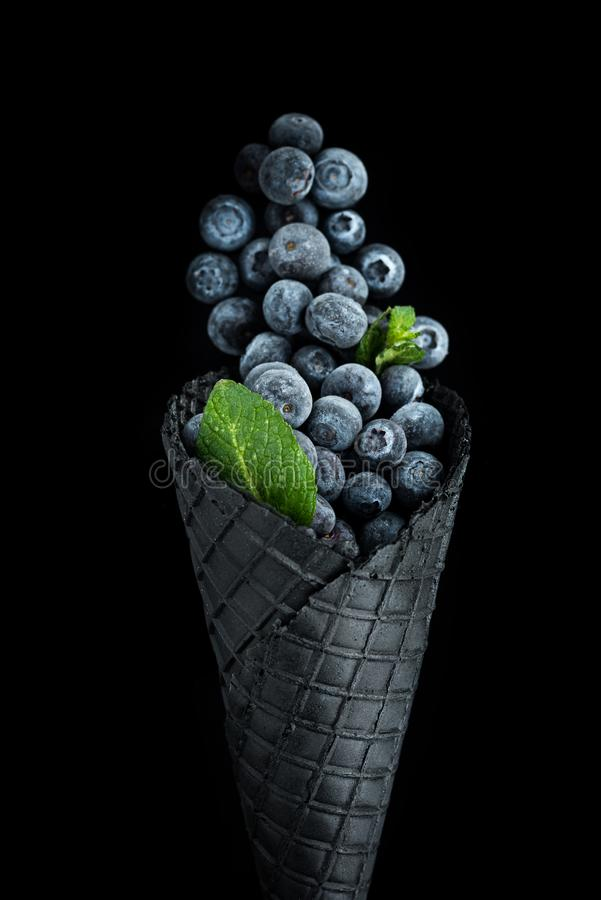 Black wafer cone with frozen blueberry fruits. Ice cream. Black wafer cone with frozen blueberry fruits. Healthy ice cream stock photo